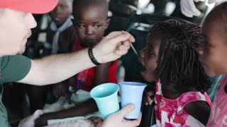 KISUMU,KENYA - MAY 19, 2018: Caucasian man treating african girls with syrup. Children opening mouth and drink medicine.