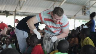 KISUMU,KENYA - MAY 19, 2018: Caucasian volunteers helping in school in Africa. Man treating sores on the head with salve.