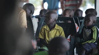 KISUMU,KENYA - MAY 19, 2018: Group of little african children sitting in the school outside and seriously looking straight.