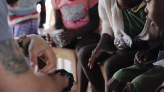 KISUMU,KENYA - MAY 19, 2018: Group of little happy children from Africa and caucasian volunteer in poor village.