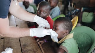 KISUMU,KENYA - MAY 19, 2018:Caucasian man in gloves helping to african children. Kids are blow out their snots in napkin.