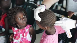 KISUMU,KENYA - MAY 19, 2018:Caucasian volunteers help in school in Africa. Man treat sores on head of girls with salve.