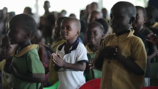 KISUMU,KENYA - MAY 19, 2018:Group of african children dancing, smiling and clapping hands after lesson in school.