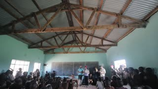 KISUMU,KENYA - MAY 21, 2018: Camera moves down. Caucasian volunteers talk at school in Africa. Children sit in classroom.