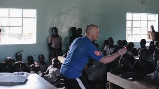 KISUMU,KENYA - MAY 21, 2018: Caucasian man shows tricks with light bulb in small African school to crowd of children