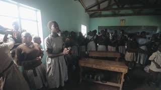 KISUMU,KENYA - MAY 21, 2018: Caucasian volunteers in poor african school. Happy boys and girls singing song, clapping hands and dancing.