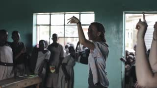 KISUMU,KENYA - MAY 21, 2018: Caucasian volunteers in poor little school in Africa. Woman dancing with group of children.