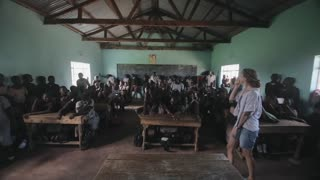 KISUMU,KENYA - MAY 21, 2018: Caucasian woman, volunteer come to classroom in african school. Boys and girls sit at desk.