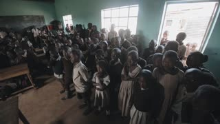 KISUMU,KENYA - MAY 21, 2018: Crowd of african children standing in big classroom. Boys and girls from poor african village.