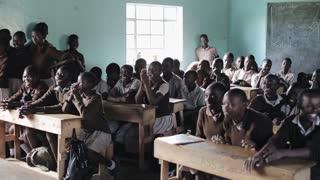 KISUMU,KENYA - MAY 21, 2018: Crowd of bald African children sitting at school desks. Boys and girls, teenagers in uniform