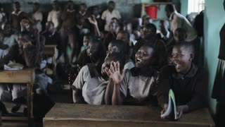 KISUMU,KENYA - MAY 21, 2018: Crowd of happy African children in school. Boys and girls, teenagers smile and laugh.