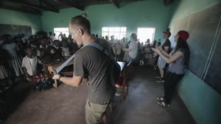 KISUMU,KENYA - MAY 21, 2018: Group of african children singing and dancing in classroom with caucasian volunteers with guitar.