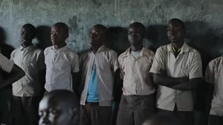 KISUMU,KENYA - MAY 21, 2018: Group of bald African guys stands near wall in the school and looks straight. Boys smiling.