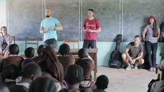 KISUMU,KENYA - MAY 21, 2018: Group of Caucasian people, volunteers in African school, talk with children, tell something