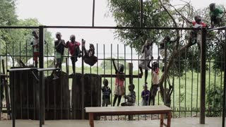 KISUMU,KENYA - MAY 21, 2018: Group of children from Africa climb and sit on fence. Boys and girls spend time outside
