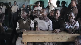 KISUMU,KENYA - MAY 21, 2018: Group of happy African children sitting in classroom and smiling, laughing together.