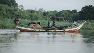 KISUMU,KENYA - MAY 21, 2018: Group of young african men sitting in boat and rows together. Males working in sea, fishing.