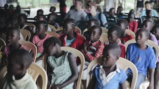 KISUMU,KENYA - MAY 21, 2018: Group of young children, boys and girls from Africa are sitting in large hall in expectation.