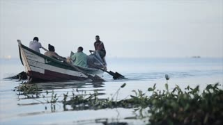 KISUMU,KENYA - MAY 21, 2018: Slow motion. Group of young african men sitting in the boat and rowing. Fisherman are working in the sea.