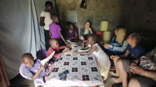 KISUMU,KENYA - MAY 23, 2018: Big group of people sitting in poor house of African family. Caucasian men and women talk