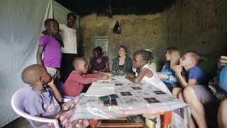 KISUMU,KENYA - MAY 23, 2018: Group of Caucasian people sitting in the house of poor African family and talking to them.