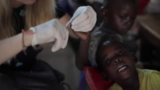KISUMU,KENYA - MAY 24, 2018: Caucasian woman helping children from Africa. Female cutting their nails with scissors.