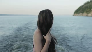 Side half-body view of a beautiful girl fixing her long black hair and enjoying the view of the river