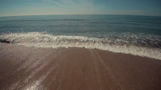 Small waves breaking on the sandy seashore. Crystal clear blue sky on the horizon