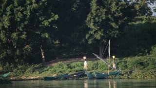 View from the boat. Two African women carrying buckets on their heads walk along the river shore, village in Africa.