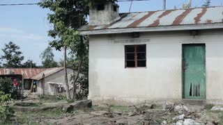 View of a small house in a poor village in Africa. Garbage lies around the destroyed building.