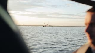 Young man is traveling on boat by sea in Africa early in the morning. Beautiful landscape, sailing boat on the horizon.