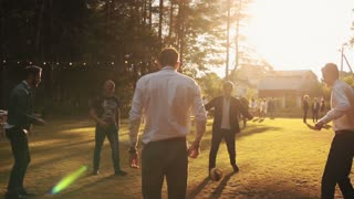 """Young men playing football at an outdoor party. Dressed-up. Suits. """"Young men playing football at an outdoor party."""