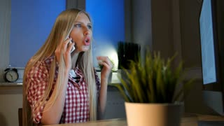Astonished woman at computer talking on smartphone. Attractive blond female sitting at wooden desk and looking with open mouth at computer monitor talking on mobile phone in dark room at night