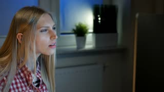 Attractive female amazed by information on monitor. Beautiful young blond woman and looking at computer monitor on wooden desk sitting in dark room at night