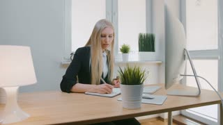 Beautiful business woman concentrating on work. Attractive young blond female in elegant jacket sitting with pen and notebook at desk with computer and looking excitedly at monitor screen.