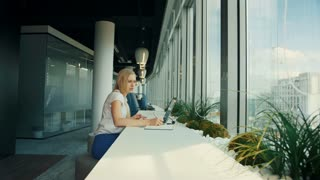 Businesswoman working with laptop in new office. Side view of woman sitting at table alongside window in modern office and using laptop in daylight.