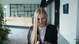 Cheerful young woman with phone in office. Pretty blond woman with long hair wearing elegant black suit and smiling charmingly at camera inside of modern office.