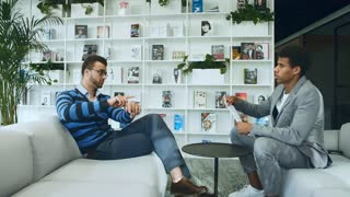 Diverse men reading documents in office. Side view of adult multiracial men exploring paper documents while sitting on sofa in modern office.