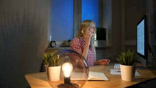 Happy female at computer talking on smartphone. Cheerful amazed blond woman in checkered shirt sitting at night at computer on wooden desk and talking on mobile phone.