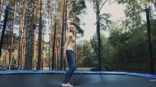 Happy female jumping on trampoline. Beautiful young blond barefoot woman in light summer shirt and jeans looking at camera and smiling jumping on large trampoline with tall trees around.