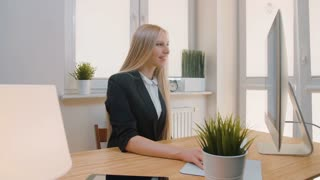 Happy female working on computer in office. Smiling attractive woman in business suit sitting at desk in light office and looking attentively at monitor screen.