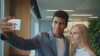 Laughing diverse coworkers taking selfie in office. Cheerful black man with laughing blond woman taking selfie with smartphone in modern office having fun