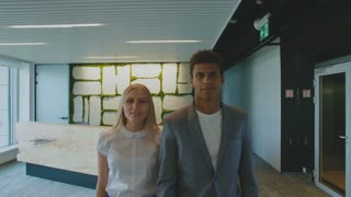 Multiethnic coworking man and woman in office. Young blond woman and African-American man in suit standing together in office looking at camera.