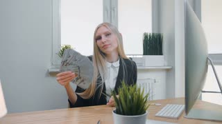 Relaxed woman with money in office. Elegant young blond female in business suit sitting at desk with computer and plant and holding in hand fan of cash confidently looking at camera.