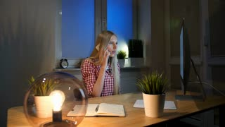 Shocked female at computer talking on smartphone. Sitting in dark room at wooden desk with notebook young blond woman talking on mobile phone and looking stunned at computer monitor.