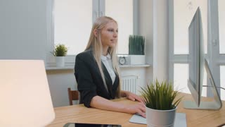 Smiling business woman showing thumbs up. Cheerful young blond female in elegant suit sitting in office at desk with computer and doing thumbs up gesture looking at camera and smiling.