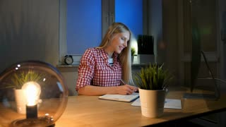 Smiling woman working on computer at night. Smiling female in checkered shirt sitting at lit by small lamp wooden desk and looking excitedly at computer monitor writing down information.