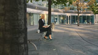 Successful business woman taking notes outdoors. Side view of elegant businesswoman sitting on bench in patio and writing in notepad while working.