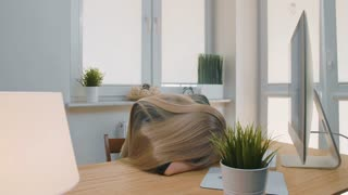 Tired woman waking up at workplace. Tired blond female office worker in elegant suit relaxing lying on arms on desk then getting up yawning and starting working on computer in light room with plants.