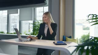 Trendy business woman watching laptop and speaking on phone. Stylish young blond woman working in office at table surfing laptop and having phone call while smiling.